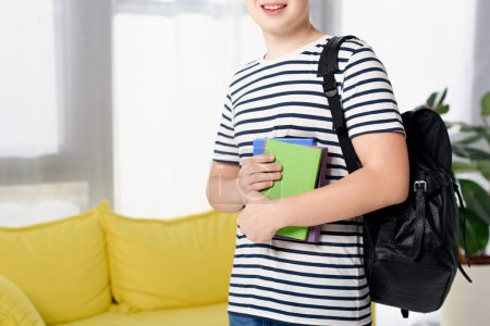 cropped image of smiling teen boy standing with books and bag at home