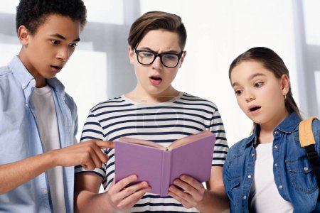 surprised multicultural teenagers looking at book at home