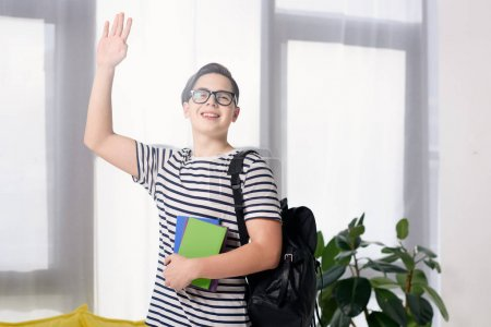 teen boy waving hand and holding books at home
