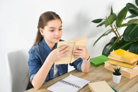 adorable preteen child reading book at home