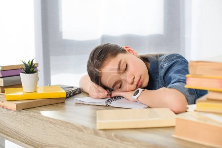adorable preteen child sleeping on books at home
