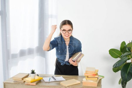 angry preteen child holding books and showing fist at home