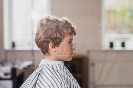 side view of little kid covered with striped cloth at barbershop