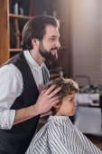 smiling handsome barber looking at reflection of little kid sitting in chair at barbershop