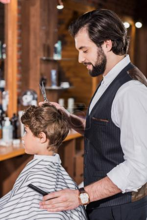 side view of little curly kid covered with striped cloth sitting at barbershop while barber cutting his hair