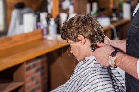 little curly kid getting haircut from barber with Hair Clipper