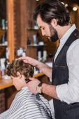 adorable curly kid getting haircut from barber with Hair Clipper