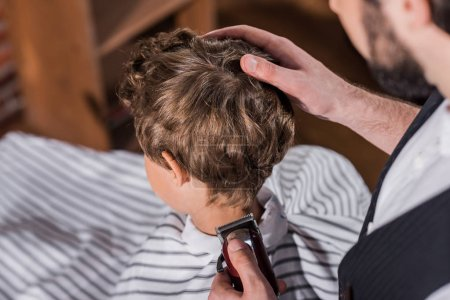 high angle view of barber cutting hair of little kid with Hair Clipper