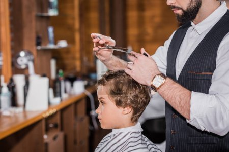 side view of barber cutting hair of curly little kid
