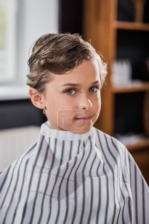 close-up shot of little kid covered with striped cloth at barbershop