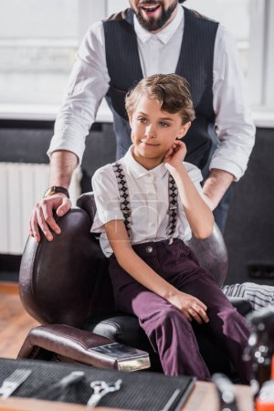 adorable little kid sitting on chair at kids barbershop with barber on background
