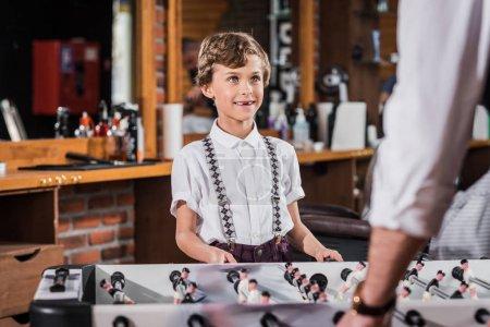 Photo pour Heureux petit garçon jouant au football de table avec père - image libre de droit