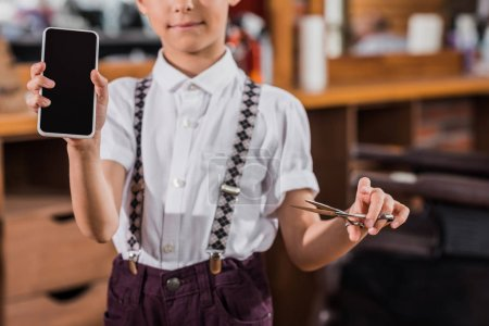 cropped shot of little kid with scissors and smartphone at barbershop