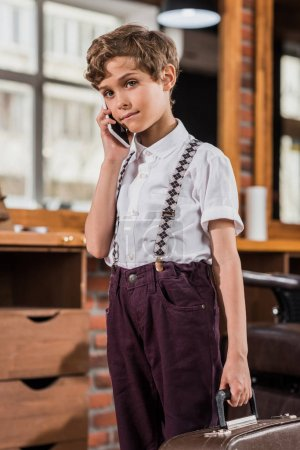 adorable little kid talking by phone at barbershop