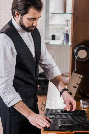 handsome young barber taking tools from rubber mat on workplace