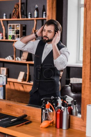 handsome young barber looking at mirror in barbershop