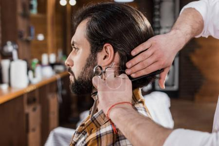 side view of handsome man getting haircut in barbershop