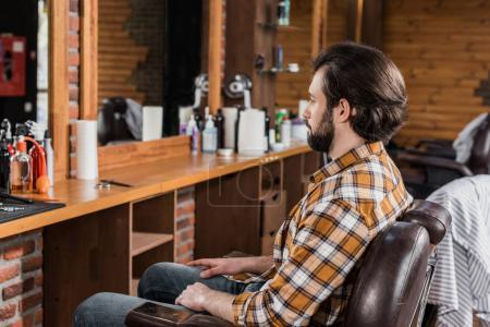 handsome bearded man in plaid shirt sitting on chair at barbershop
