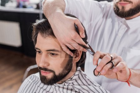 smiling bearded man getting haircut in barbershop