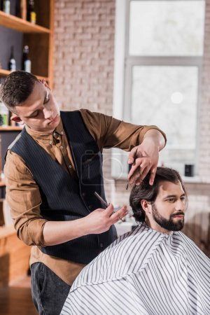 bearded young man covered with striped cloth getting haircut from professional barber at barbershop
