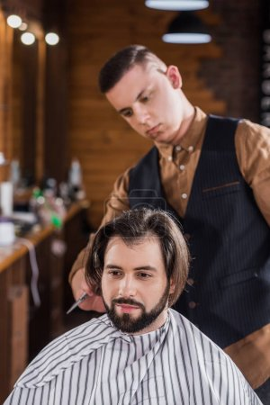 bearded young man getting haircut from professional barber at barbershop