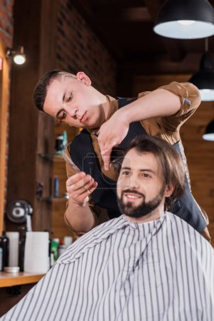 happy young man getting haircut from professional barber at barbershop