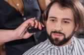 close-up shot of smiling young man getting haircut at barbershop