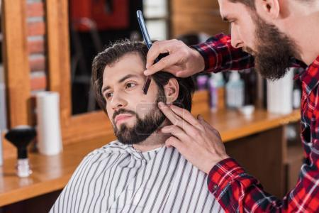 young barber in plaid shirt shaving man with Hair Cutting Machine