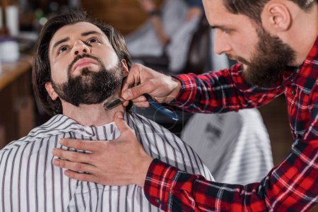 close-up shot of young barber shaving man with Hair Cutting Machine