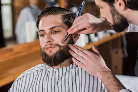 close-up shot of barber shaving man with straight razor