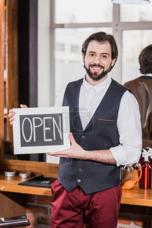 happy bearded barber holding open signboard in front of workplace