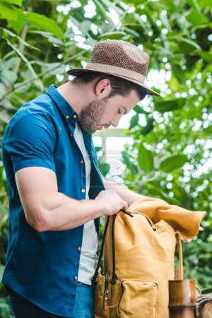 handsome young man in straw hat looking inside of backpack while hiking in forest