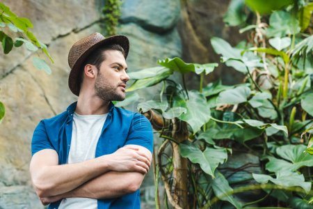 young man in straw hat and stylish clothes in rainforest