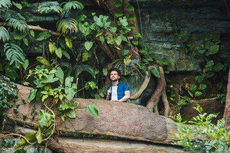 Photo pour Vue de dessous d'attirant jeune homme de vêtements élégants et chapeau de paille de randonnée en forêt tropicale - image libre de droit