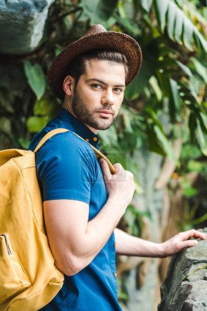attractive young man in stylish clothes in rainforest