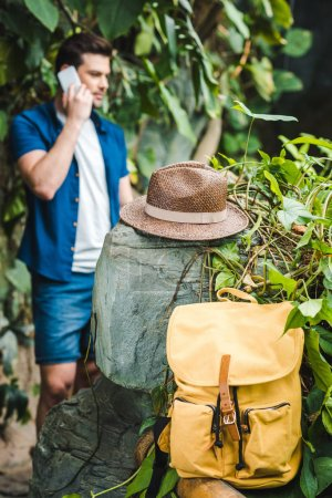 handsome young man talking by phone in rainforest with backpack and straw hat on foreground