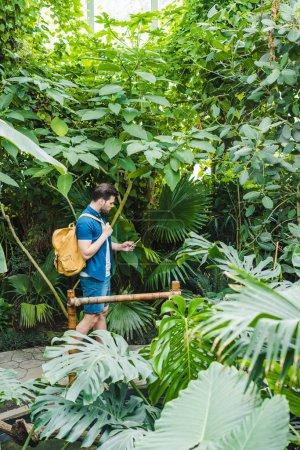 Foto de Atractivo joven en ropa elegante con smartphone en parque lleno de plantas exóticas - Imagen libre de derechos