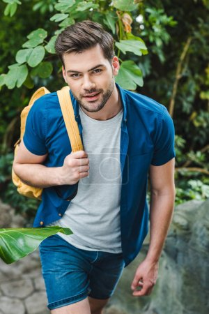 smiling young man in stylish clothing with backpack walking in park