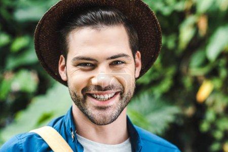 Photo pour Portrait en gros plan d'un jeune homme souriant en chapeau de paille sur la nature - image libre de droit