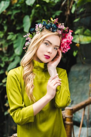 beautiful young woman with floral wreath looking at camera