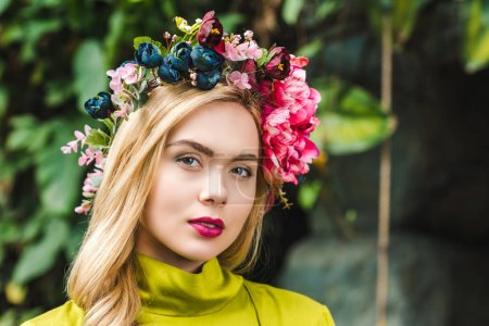 close-up portrait of beautiful young woman with floral wreath looking at camera