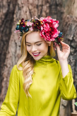 smiling young woman with floral wreath looking down