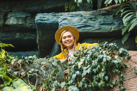 bottom view of happy young woman in straw hat looking at camera in jungle