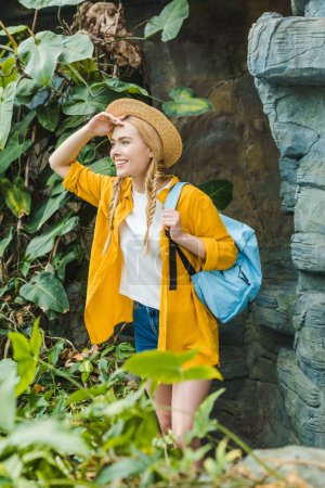 happy young woman in straw hat with backpack hiking in jungle