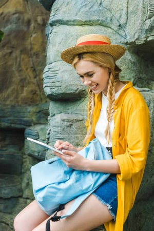 smiling young woman in straw hat using tablet while sitting on rocks outdoors