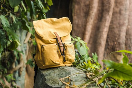 Photo pour Gros plan tiré du sac à dos jaune vintage sur rocher dans la jungle - image libre de droit