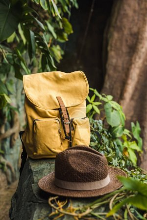 close-up shot of vintage yellow backpack and straw hat on rock in jungle