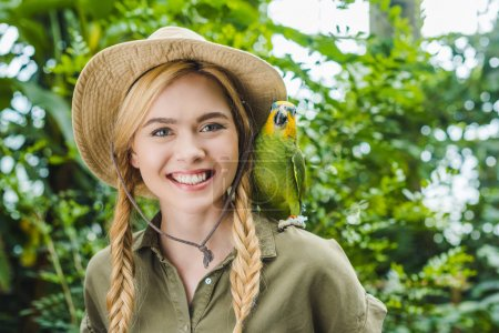 happy young woman in safari suit with parrot on shoulder in jungle