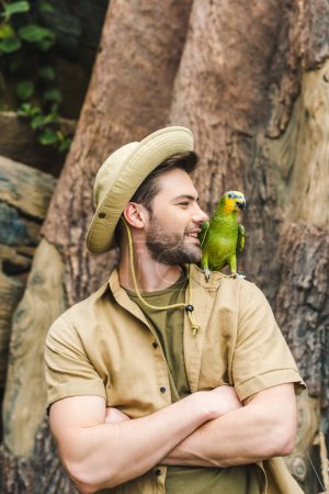 handsome young man with parrot on shoulder and crossed arms in jungle