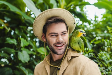 handsome young man with parrot on shoulder
